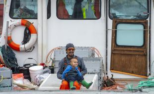 A Mi'kmaw fisherman hold his son on his boat before heading out to set traps in Saulnierville, Nova Scotia on October 21, 2020.